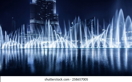 Beautiful famous fountain in Dubai at night, romantic music, water dance, blue lights, luxury resort, evening cityscape