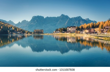 Beautiful famous Misurina lake at sunset in autumn in Dolomites, Italy. Landscape with lake, mountains, blue sky reflected in water, buildings, colorful forest in italian alps. Travel and nature