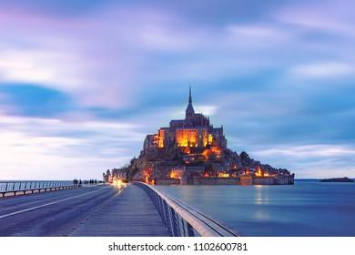 Beautiful famous Mont Saint Michel with bridge during evening blue hour, Normandy, France
