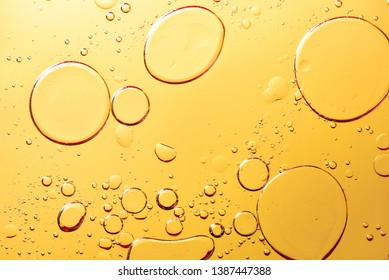 Beautiful and fantastic macro photo of water droplets in oil with a yellow background.
