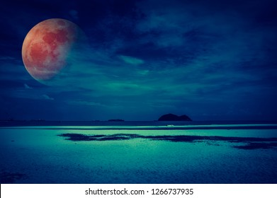 Beautiful fantasy tropical beach of seascape in night. Attractive red super moon or blood moon on dark sky with cloud. Serenity nature background. Vintage filter effect.