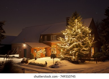 A beautiful farm house with a tall christmas tree and a lot of fresh snow at night.