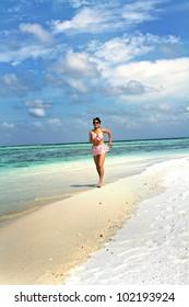 Beautiful fashion asian girl running along beach in Maldive in hot summer
