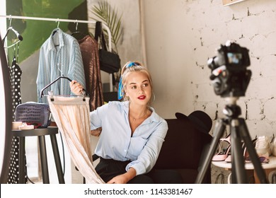Beautiful fashion blogger holding skirt on hanger dreamily recording new fashion video for vlog with clothes rack on background