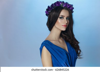 A beautiful fashion brunette model with splendid make up and curly long hair and crown with violets flowers on her head, in blue dress, looking at camera. Horizontal  portrait on the blue background.