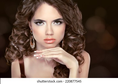 Beautiful fashion brunette woman model with wavy long hair and fashion earrings. Professional makeup.