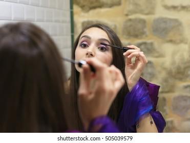 Beautiful fashion girl doing makeup