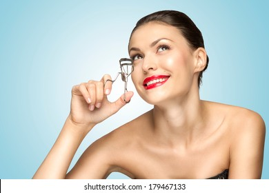 A beautiful fashion girl holding an eyelash curler in her hand as a makeup accessory.