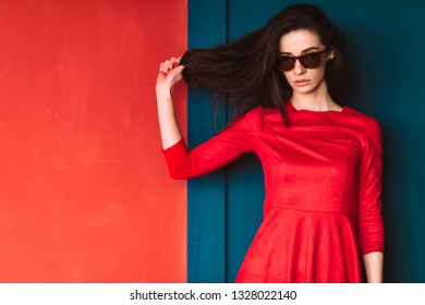 Beautiful fashion girl with long hair, spanish appearance in sunglasses and red elegant dress posing on blue red wall in studio. Amazing babe in suglasses pulling her black hair. Hairstyle advertsing