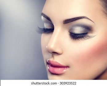 Beautiful Fashion Luxury Makeup, long eyelashes, perfect skin facial make-up. Beauty Brunette model woman holiday make up close up. Eyelash extensions, false eyelashes.