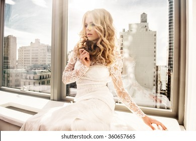 Beautiful fashion model bride sitting near the window with city view wearing white wedding dress