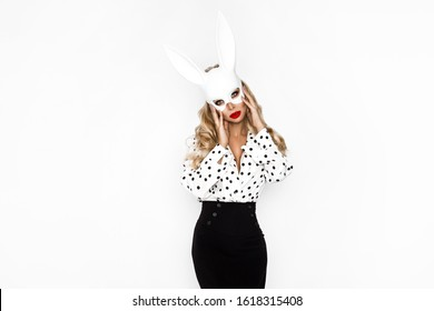 Beautiful fashion model, dressed in pinup style clothing in polka dot and Easter bunny mask,, isolated over white background. Fashionable Easter costume blond girl.