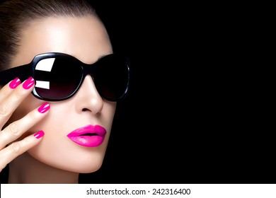Beautiful fashion model face with oversized black sunglasses. Bright makeup and manicure. High fashion portrait isolated on black background with copy space for text. Beauty and fashion concept.