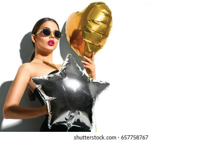 Beautiful fashion model girl with colorful heart and star shaped balloons posing in studio in sunglasses, isolated on white background. Beauty gorgeous woman celebrating. Holiday make up, accessories