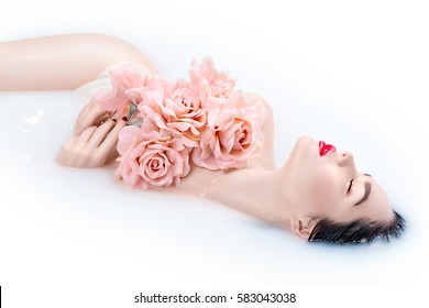 Beautiful Fashion model girl in milk bath, spa and skin care concept. Beauty young Woman with bright makeup and pink rose flowers relaxing in milk bath. Rejuvenation, skin pampering, treatment.