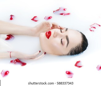 Beautiful Fashion model girl in milk bath, touching face skin, spa and skin care concept. Beauty young Woman with red rose flower relaxing in milk bath. Healthy Face and hands, rejuvenation.