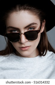 Beautiful fashion model with glasses and black hat in studio