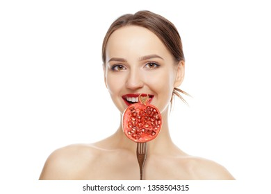 Beautiful fashion model with perfect skin, natural makeup and red lips with pomegranate isolated on white background