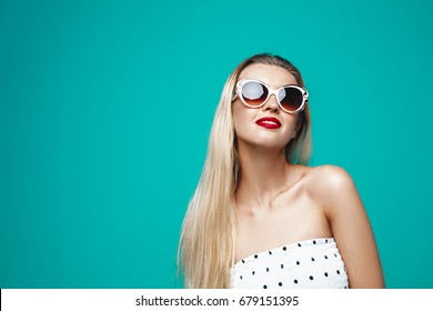 Beautiful fashion model portrait. Summer stylish girl on sunglasses on blue turquoise background. Cheerful young woman on white dress.