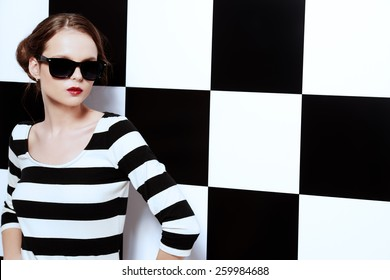 Beautiful fashion model posing in dress in black and white stripes on a background of black and white squares. Beauty, fashion concept. Business style.