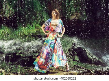 Beautiful fashion model posing in front of the waterfall