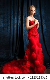 Beautiful fashion model in a red evening dress on a dark blue background