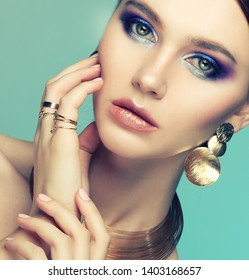 beautiful fashion model wearing elegant jewelry in color light