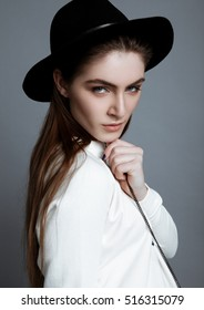 Beautiful fashion model in white with black hat in studio