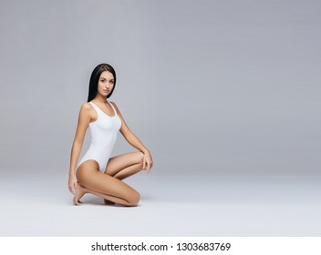 Beautiful fashion model in white swimsuit and hosiery. Young and beautiful woman posing in studio.