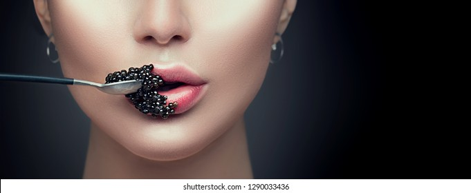 Beautiful Fashion Model woman eating black caviar. Beauty girl portrait with caviar on her lips. Fashion female with spoon of black Caviar isolated on Black background