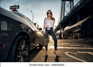 Beautiful fashion model woman posing with a car wearing causual street style outfit