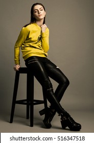 Beautiful fashion model with yellow jumper sitting in studio