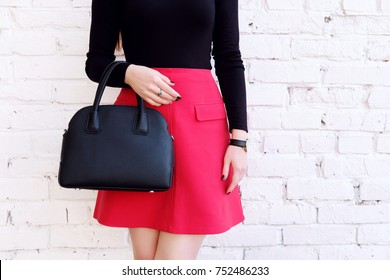 Beautiful fashion outfit, red skirt and black big leather bag in hand of girl . Stylish accessory