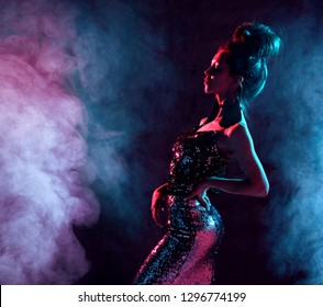 Beautiful fashion sexy brunette woman posing in blue and pink neon light in fashion gold sparkle dress on dark background