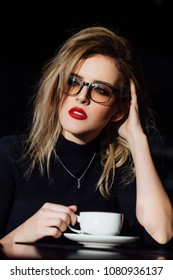 Beautiful fashion stylish girl sits in a cafe with a cup of coffee in glasses. Hipster blonde, red lips,black blouse. Atmospheric creative portrait. drinks tea and thinks about it. Treble clef pendant