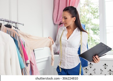 Beautiful fashion stylist is selecting clothing for her client. She is holding a folder of documents and smiling. The woman has a tape-measure over her neck