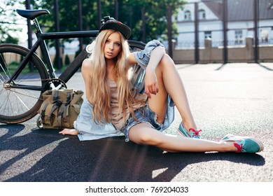 Beautiful fashion urban hipster blonde woman posing in summer on the street with sport style bicycle and travel backpack