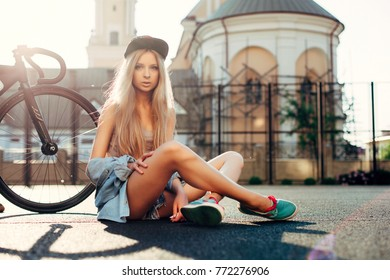 Beautiful fashion urban hipster blonde woman posing in summer on the street with sport style bicycle