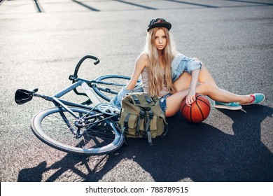 Beautiful fashion urban hipster blonde woman posing in summer on the playground with sport style bicycle, basketball ball and travel backpack