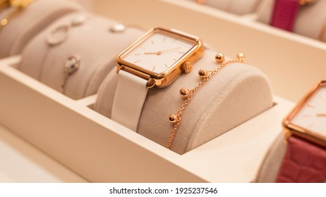Beautiful fashion watch with leather strap and a gold bracelet in the shop window