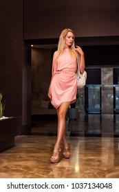 beautiful fashion woman in asymmetrical gently pink dress in dark interior of hotel holl