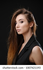 Beautiful fashion woman in black classical costume, with long hair and make up, posing at black studio background
