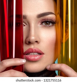 Beautiful fashion woman with  a colored  items.  Attractive white girl with living coral lipstick. Glamour fashion model with bright gloss make-up posing at studio. Stylish fashionable concept. Art.