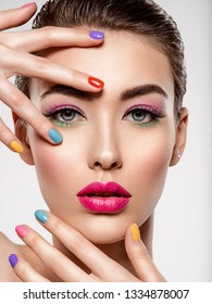 Beautiful fashion woman with a colored nails. Attractive white girl with multicolor manicure. Glamour fashion model with bright gloss make-up posing at studio. Stylish fashionable concept. Art