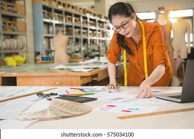 beautiful fashion woman designer choice looking for best match market design sketch with fabric sample in manufacturing office studio. profession and job occupation concept.