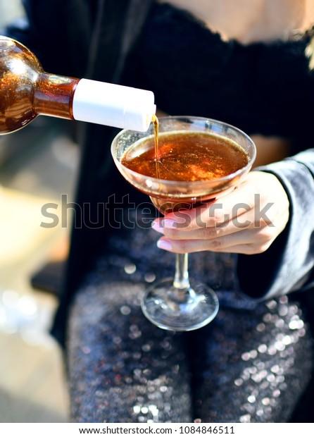 Beautiful fashion woman drink gold glitter martini cosmopolitan cocktail in restaurant cafe