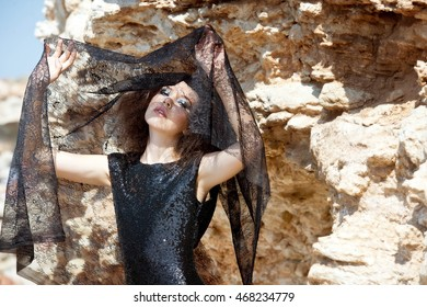 Beautiful fashion woman in shining black dress on the rocks. Fashion portrait