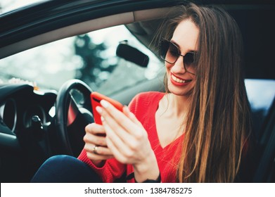 Beautiful fashion woman smiling while sitting in the car and using a cell phone. Girl typing message in a smartphone. Nice beautiful young woman use mobile phone touching the screen inside the car