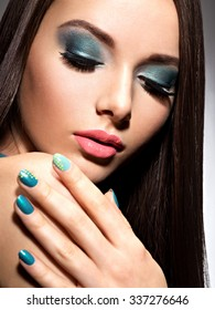 Beautiful fashion woman with turquoise make-up and nails  - on white background
