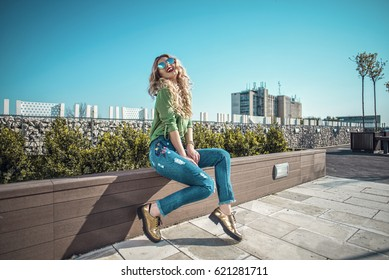 Beautiful fashion woman wearing jeans, sitting on the rooftop terrace
